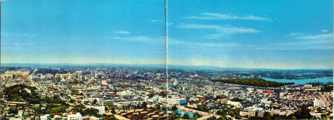 Panoramic view of Tokyo looking east-northeast from Tokyo Tower, c. 1960. The Imperial Palace grounds are at left; the wooded Hama Detached Palace is at right, astride Tokyo Bay.