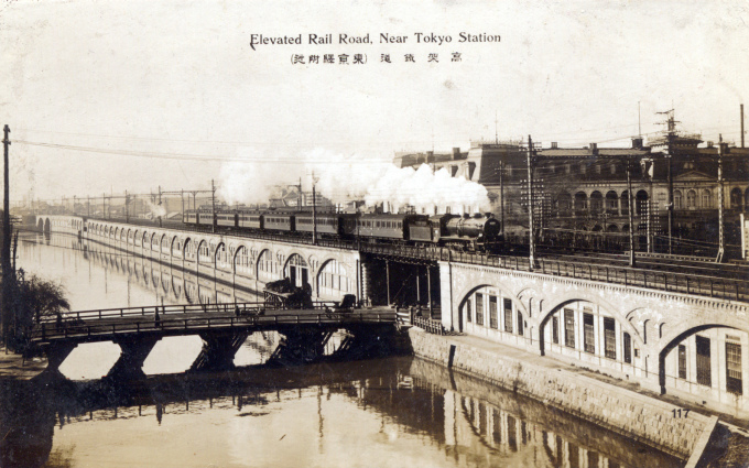 A C51 locomotive pulling Tokaido Main Line carriages past the Imperial Hotel, at Yamashitacho-bashi, on arrival into Tokyo, c. 1920.