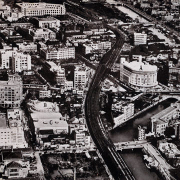 Aerial view of Yurakucho, c. 1935. In 1933, three high-class theaters of several thousand seats were built in Tokyo's Yurakucho district, within easy walking-distance of the station (at center), by property magnate Kobayashi Ichizo, who had made his money developing the Osaka-Kobe railway and organizing the all-girl Takarazuka Revue at Takarazuka, Japan. In the image above, c. 1935, the three were clustered together near the Imperial Hotel (partially visible at lower-left), including the Hibiya Eiga Gekijo (B), Yurakuza Theater (C), and the Toho (aka Takarazuka) Gekijo (D) within easy walking distance of Yurakucho Station near the 4000-seat Nichigeki Theater (A).