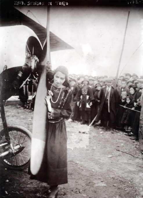 Photograph of Katherine Stinson in Tokyo, c. 1916, priming the engine of her airplane.